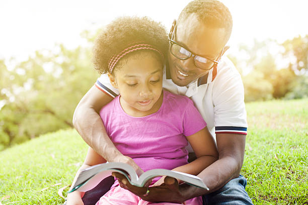 African American family reading a book together in the park stock photo