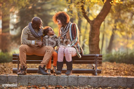 istock African American family relaxing on bench in the autumn park. 510690040
