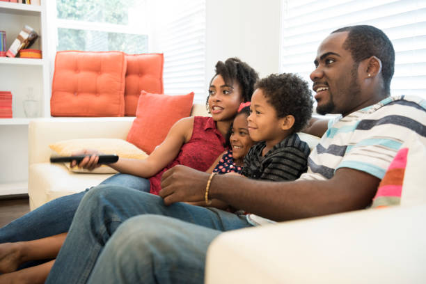 African American family sitting on sofa watching tv stock photo