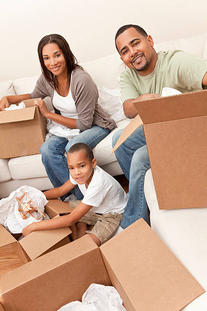 african american family unpacking boxes moving house - happy mom packing some toys stock photos and pictures