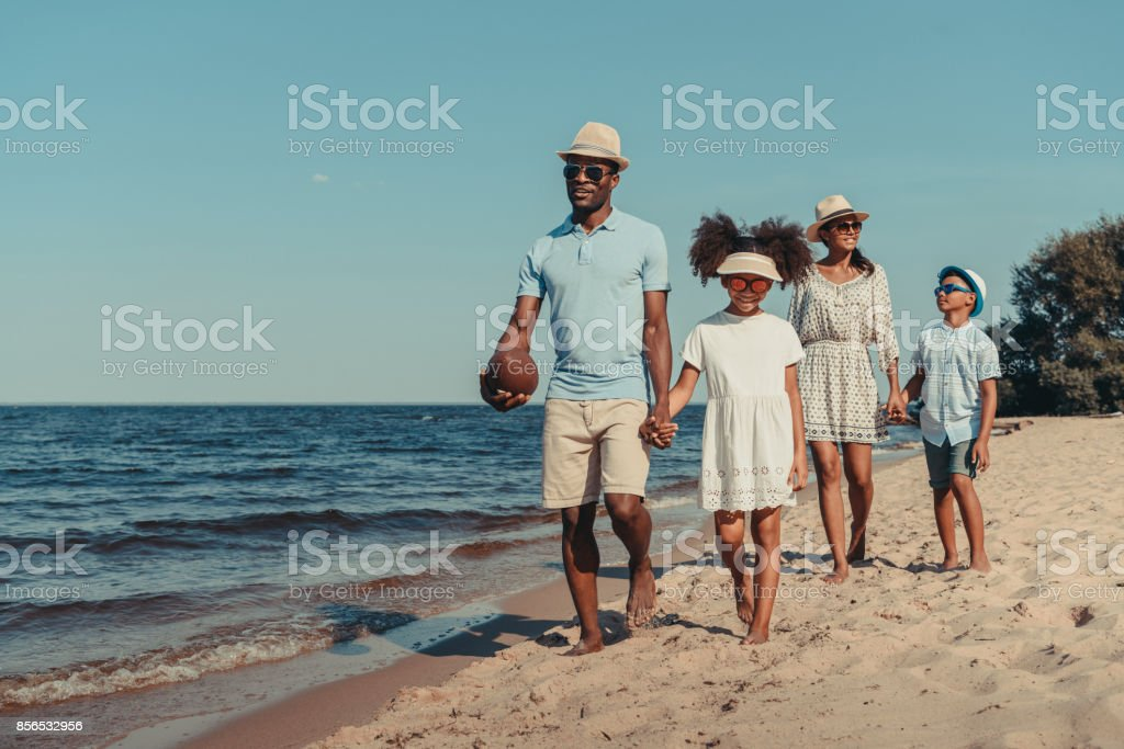 african american family walking on beach stock photo