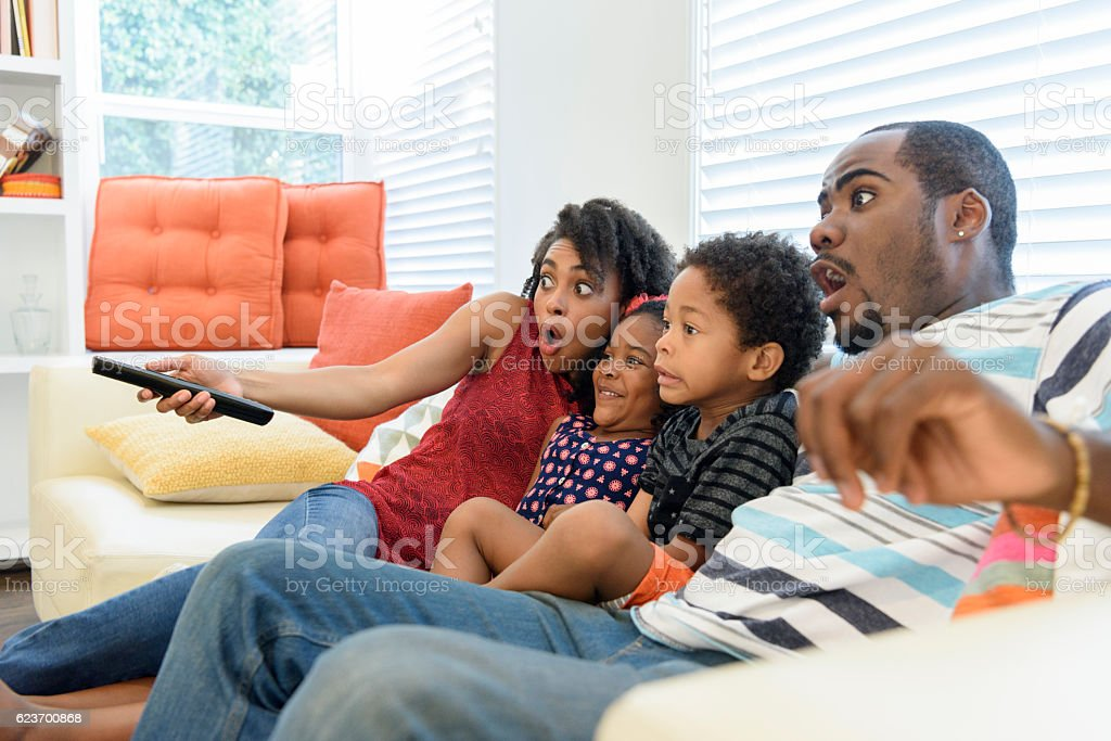 African American family watching television together stock photo
