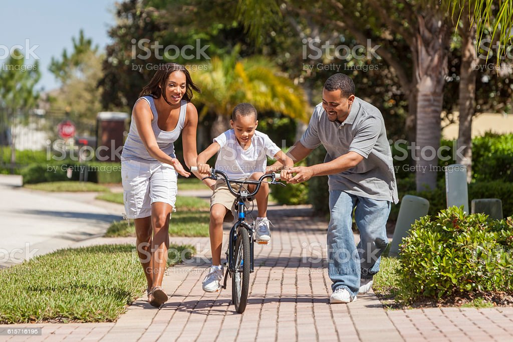 African American Family WIth Boy Riding Bike & Happy Parents stock photo
