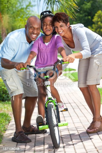 istock African American Family WIth Girl Riding Bike & Happy Parents 137108048