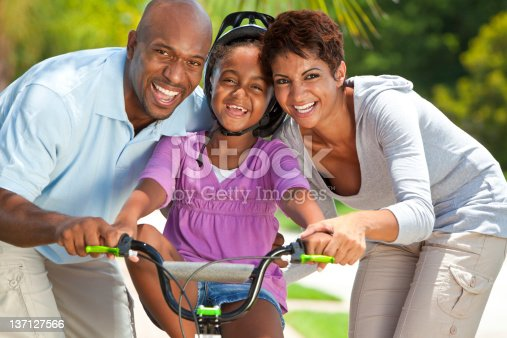 istock African American Family WIth Girl Riding Bike & Happy Parents 137127566