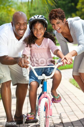 istock African American Family WIth Girl Riding Bike & Happy Parents 137144104
