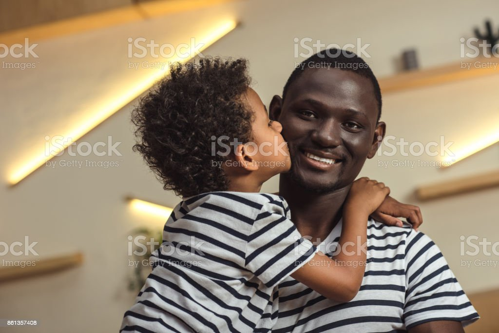 african american father and child hugging stock photo