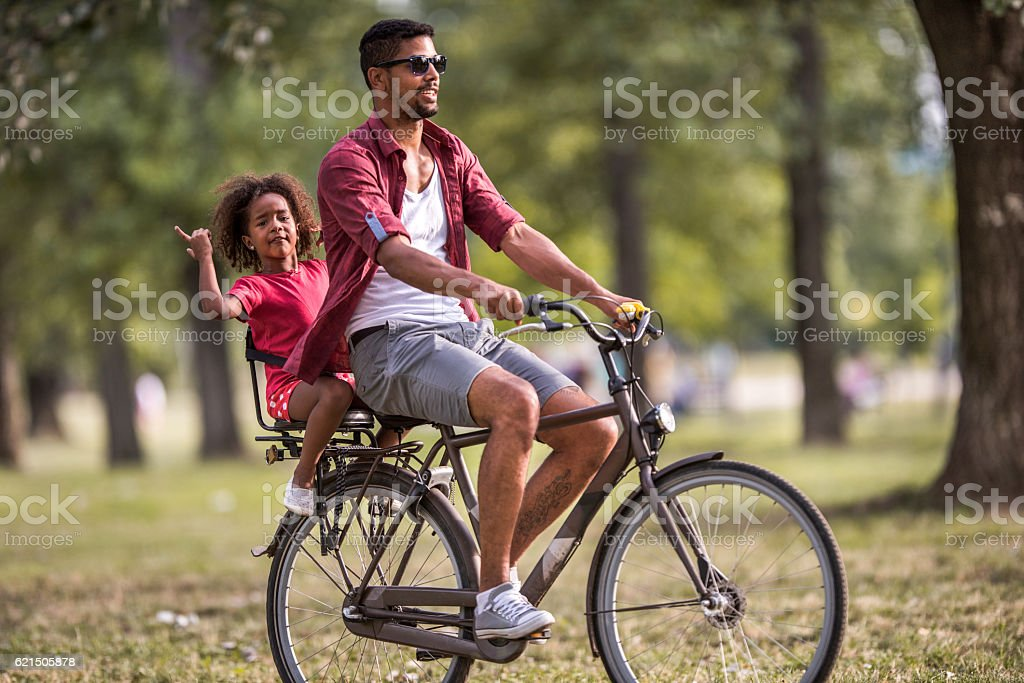 African American father and daughter on a bike in nature. Lizenzfreies stock-foto