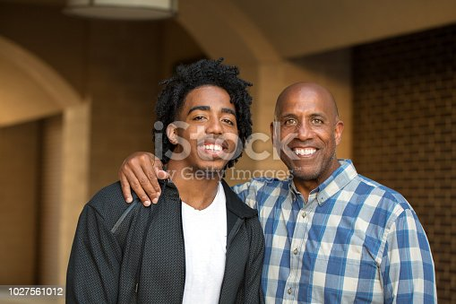 African American father and his adult son talking and laughing.