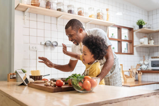 padre afroamericano e figlio piccolo che fanno videochiamata con tablet digitale e agitano le mani ridendo parlando con la famiglia mentre cucinano in cucina. la famiglia nera si diverte mentre il virus pandemico a casa - cucinare foto e immagini stock