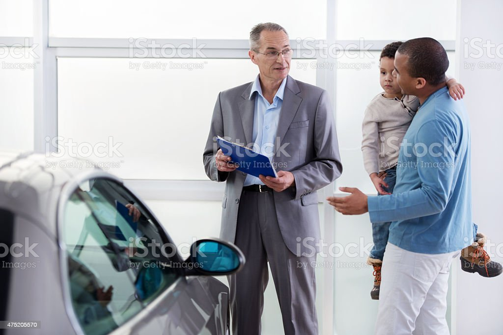 African American father and son discussing with a car salesperson. stock photo