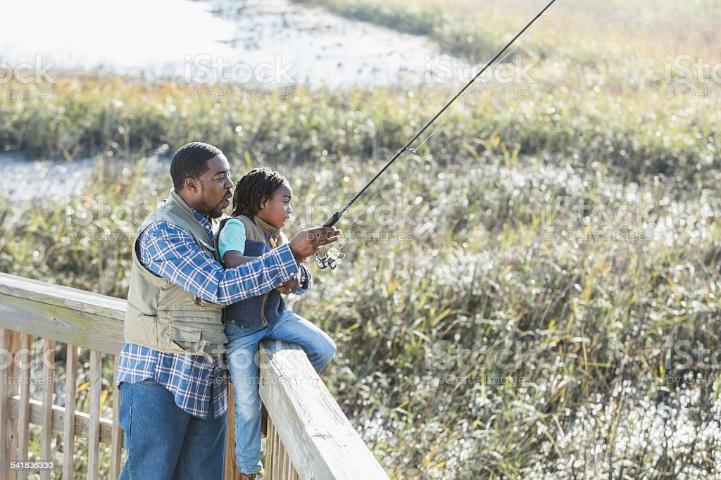 African American father and son fishing together stock photo