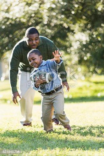istock African American father and son playing football 521545738