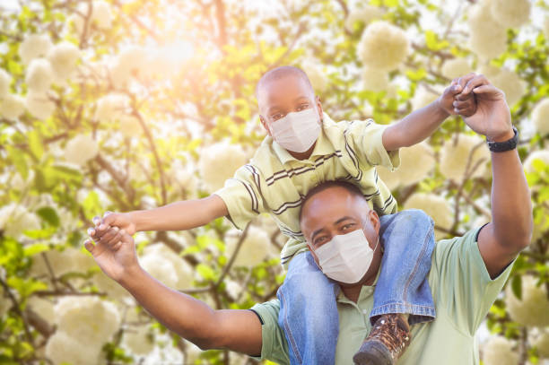 African American Father And Son Playing Outdoors Wearing Medical Face Mask stock photo