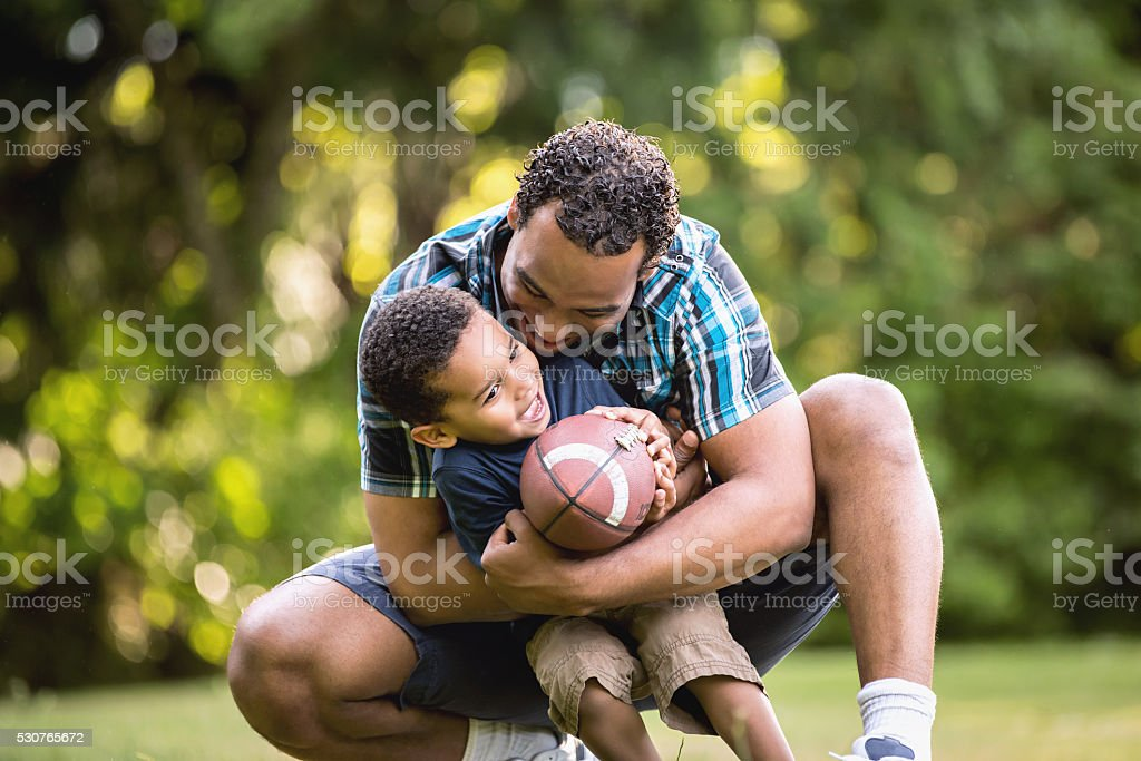 African American Father and Young Son outdoors playing football royalty-free stock photo