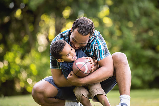 African American Father and Young Son outdoors playing football stock photo