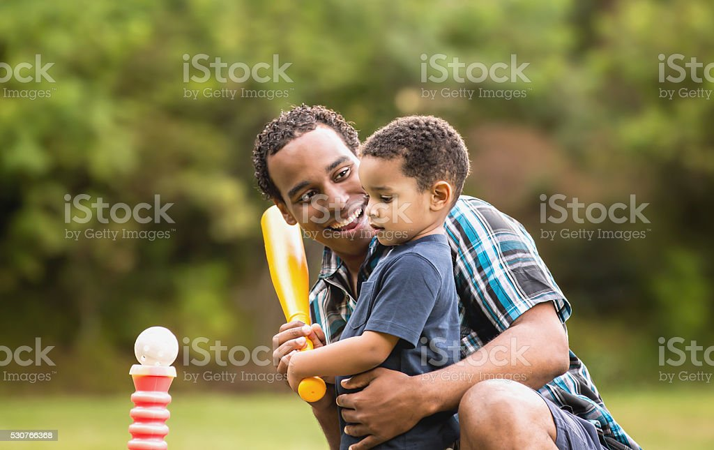 African American Father and Young Son outdoors playing T Ball stock photo