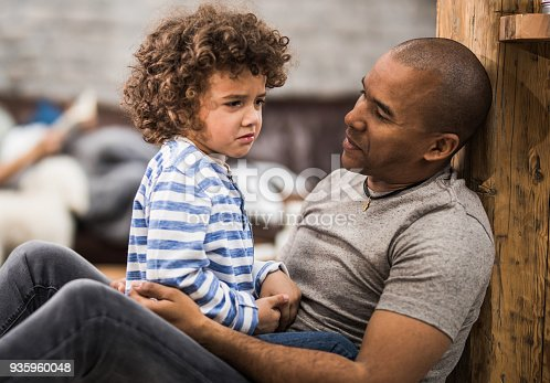istock African American father consoling his small sad son at home. 935960048