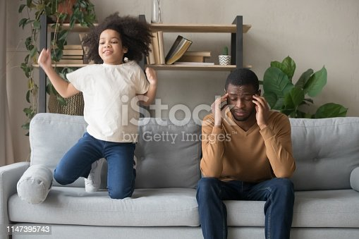 African American father having problem with noisy naughty preschool daughter jumping on couch and screaming, demanding attention, child tantrum manipulation concept, tired dad touching temples