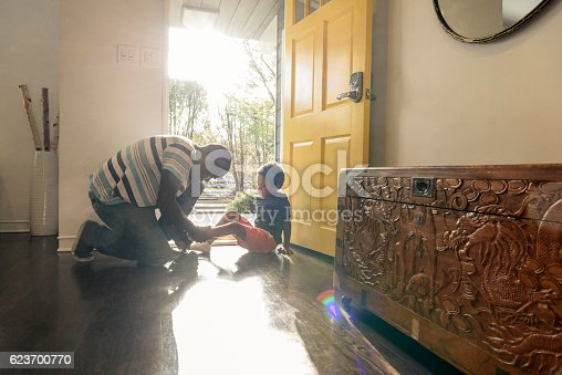 The young boy is sitting on the floor in sunlight as his father helps him put his shoe on