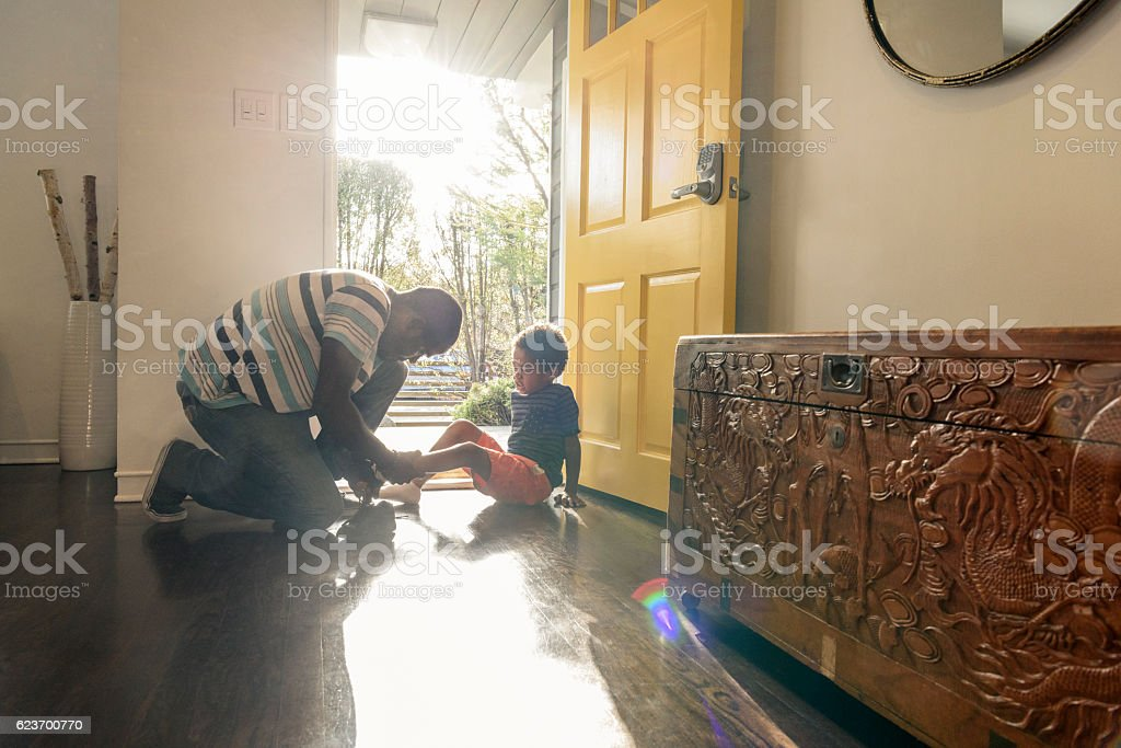 African American father helping son with shoes by front door stock photo
