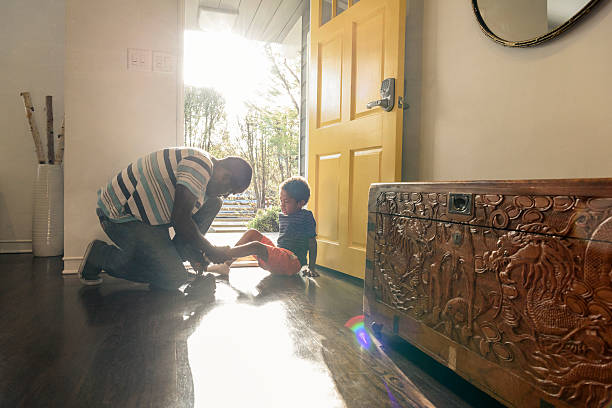 african american father helping son with shoes by front door - haushaltshilfe stock-fotos und bilder