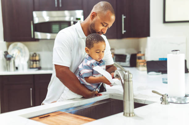African American father helps his son wash his hands stock photo