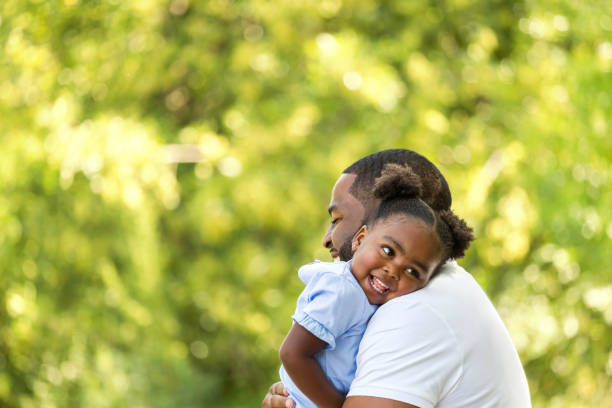 African American father hugging her daughter. African American father and daughter. one parent stock pictures, royalty-free photos & images