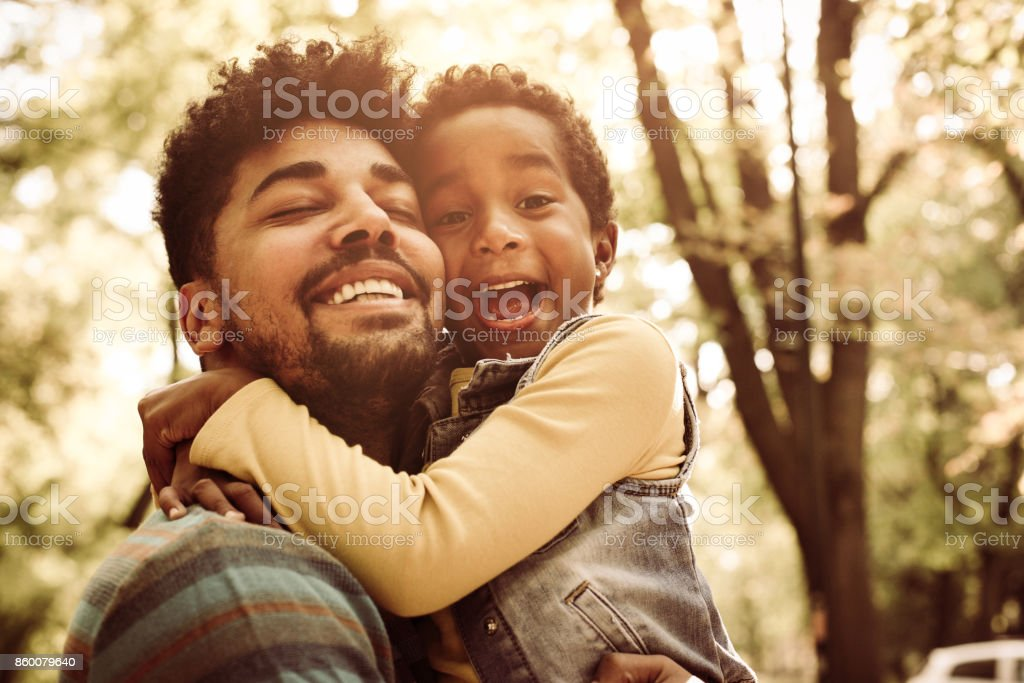 African American father hugging little daughter in park. stock photo