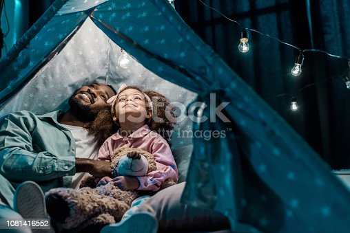 african american father looking up with daughter in wigwam in living room