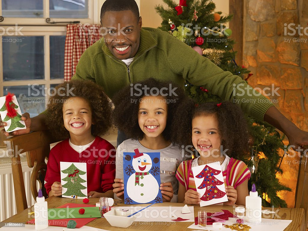 African American father making Christmas cards with children stock photo
