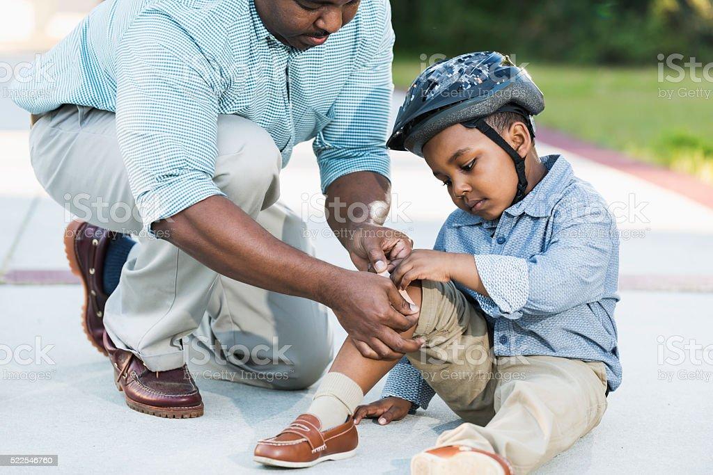 Père afro-américain de mettre sur son bandage du genou - Photo