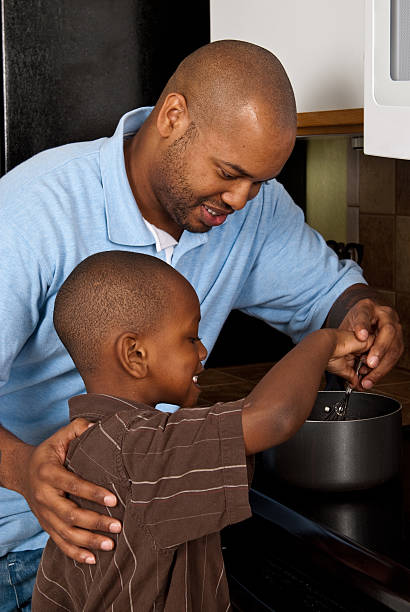 African American father teaching son to cook stock photo