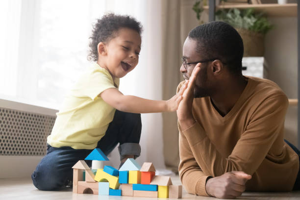 African American father with toddler son playing with wooden constructor African American father in glasses with toddler son playing with colorful wooden constructor, giving five, adorable little child and black dad or babysitter having fun on warm floor at home toddler stock pictures, royalty-free photos & images