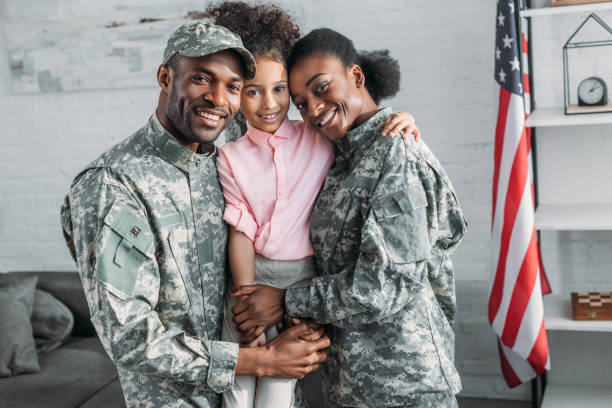 African american female and male soldiers embracing their daughter African american female and male soldiers embracing their daughter military stock pictures, royalty-free photos & images