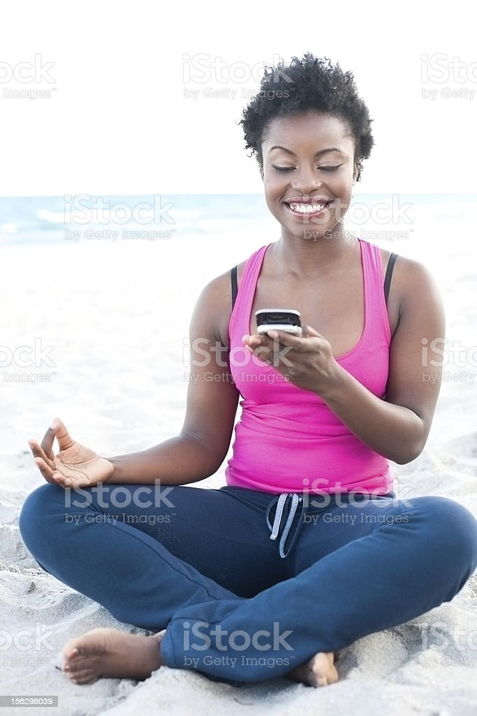 African American female at the beach text messaging royalty-free stock photo