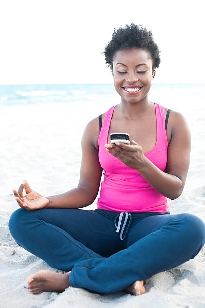 African American female at the beach text messaging stock photo