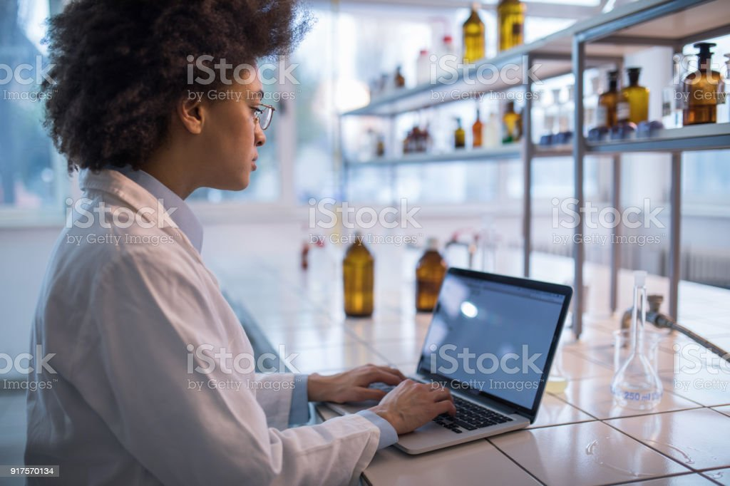 African American female biotechnologist working on laptop in a laboratory. stock photo
