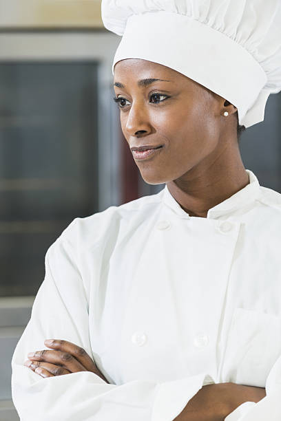 African American female chef in commercial kitchen An African American female chef standing with arms folded wearing a uniform, in a commercial kitchen. The woman, in her 30s, is a successful owner of a minority run business. chef's whites stock pictures, royalty-free photos & images