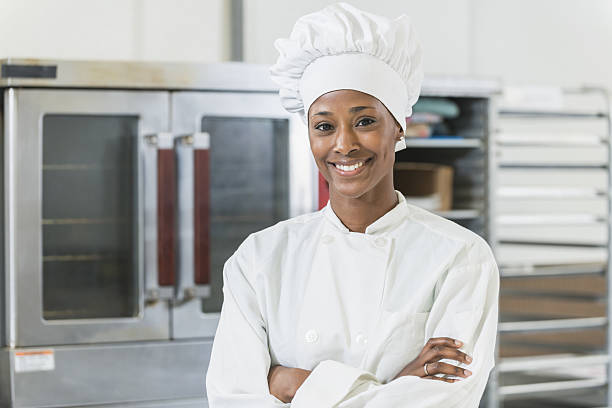 African American female chef in commercial kitchen stock photo