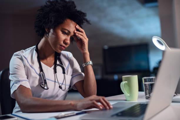 afroamericano mujer médico con dolor de cabeza trabajando en ordenador portátil. - trabajar hasta tarde fotografías e imágenes de stock