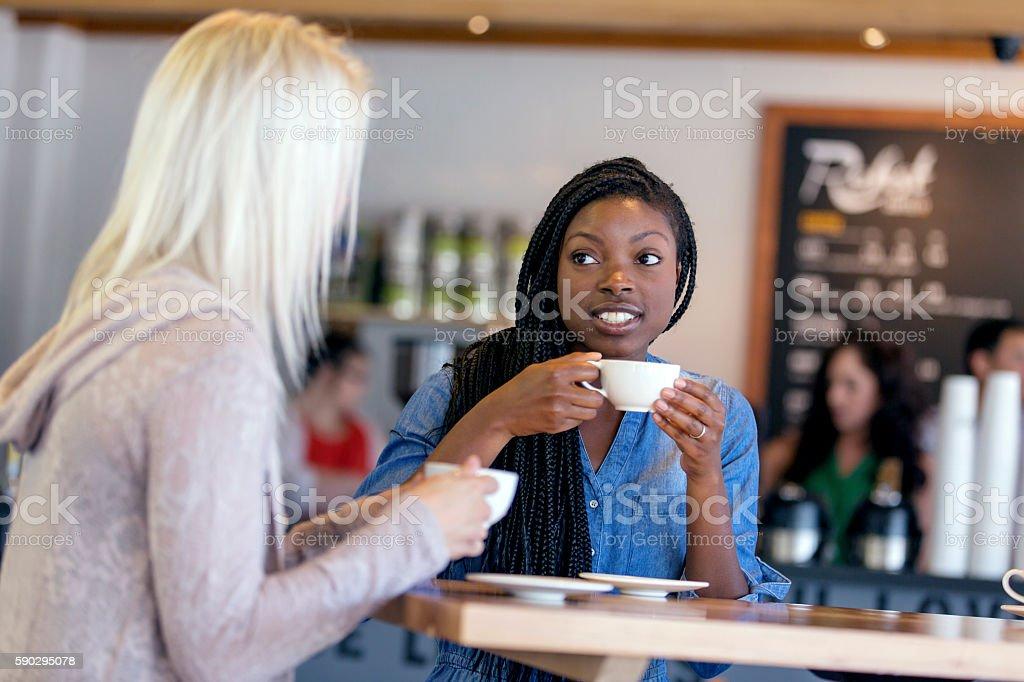 African American female drinking coffee with a friend Стоковые фото Стоковая фотография
