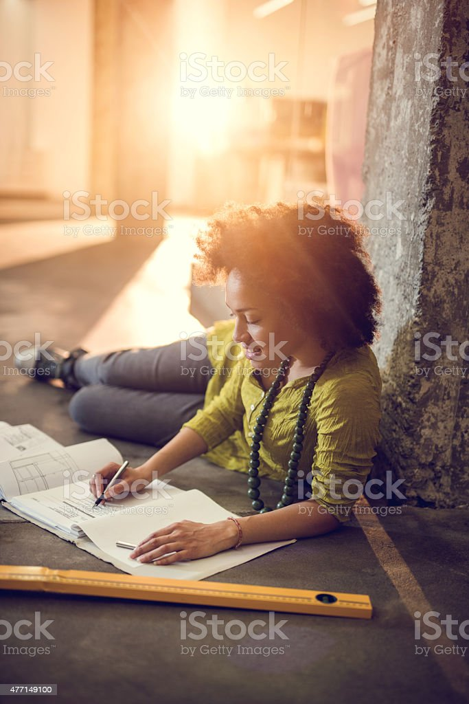 African American female engineer working on construction plans. stock photo