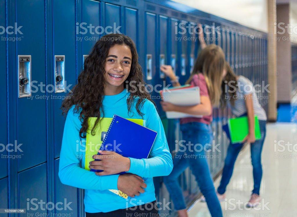 Retrato de estudiante de secundaria femenina afroamericana, sonriendo en un pasillo de la escuela - foto de stock