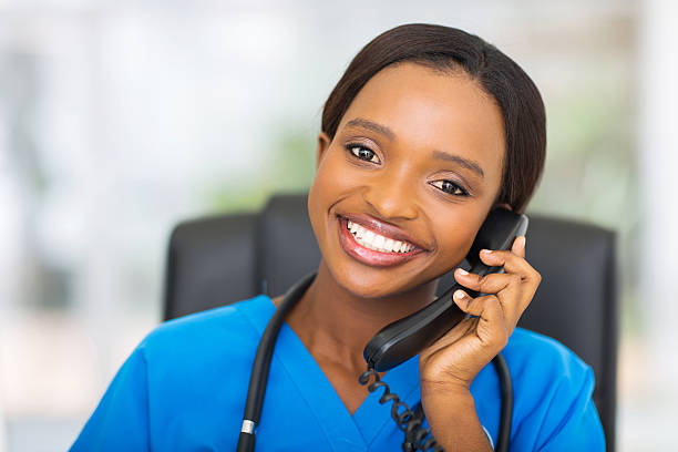 african american female nurse using landline phone - nurse on phone stock photos and pictures