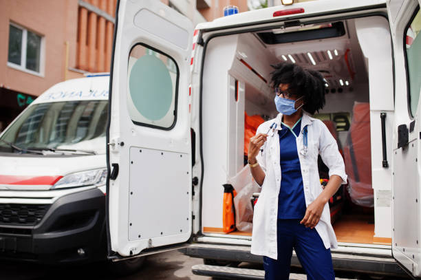 African american female paramedic in face protective medical mask standing in front of ambulance car. stock photo
