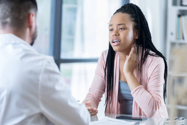 African American female patient talks with doctor about her symptoms stock photo