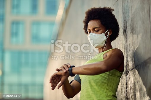 Black athletic woman with protective face mask using smart watch while checking her heart rate after running outdoors.