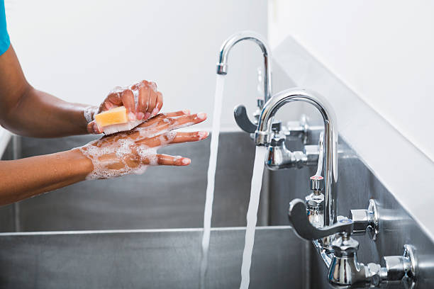 African American female surgeon washing hands stock photo