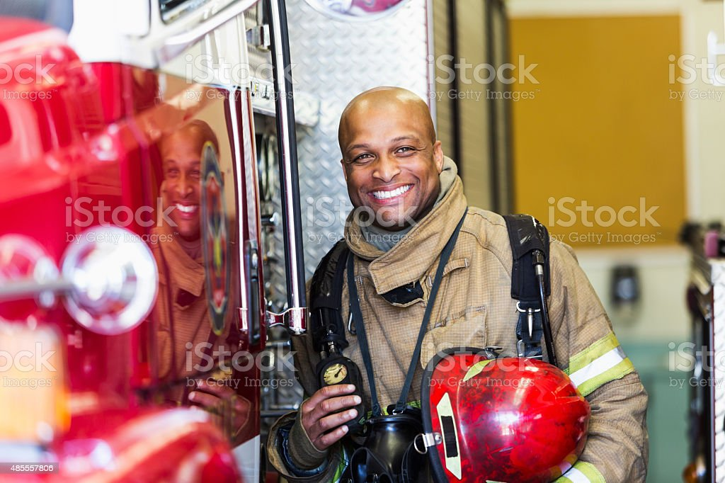 African American fire fighter standing next to truck stock photo